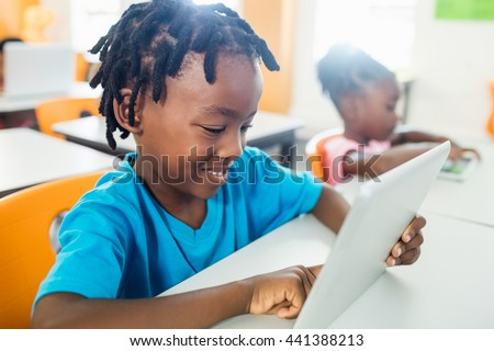 Side view of pupil using tablet pc in classroom at elementary school