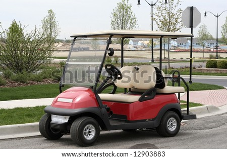 Side view of red golf cart - stock photo