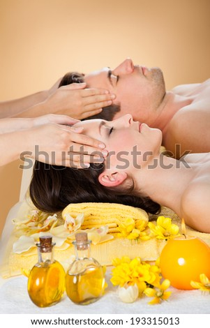 Side view of relaxed young couple receiving head massage at spa