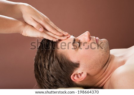 Side view of relaxed young man receiving forehead massage in spa - stock photo