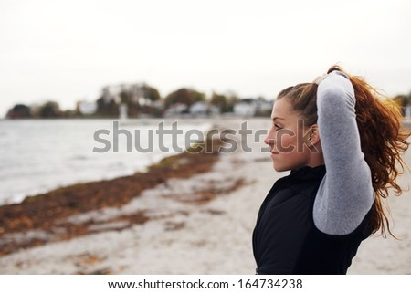 Side view of relaxed young woman looking away at sea. Beautiful caucasian female model looking at copyspace on beach. Fit and healthy female athlete resting after workout. - stock photo