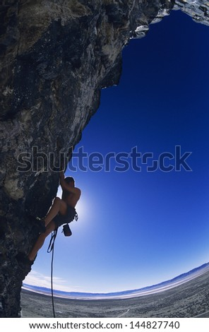 Side view of rock climber climbing up a cliff against clear blue sky - stock photo