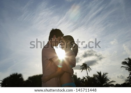 Side view of romantic teenage couple hugging on beach at sunset - stock photo