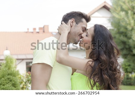 Side view of romantic young couple kissing outdoors - stock photo