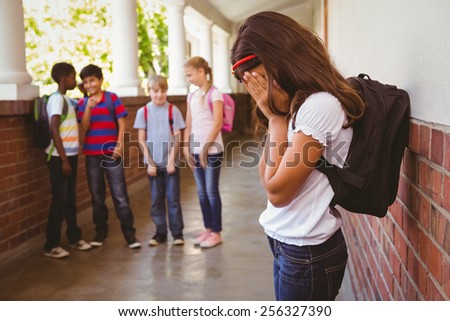 Side view of sad schoolgirl with friends in background at school corridor - stock photo