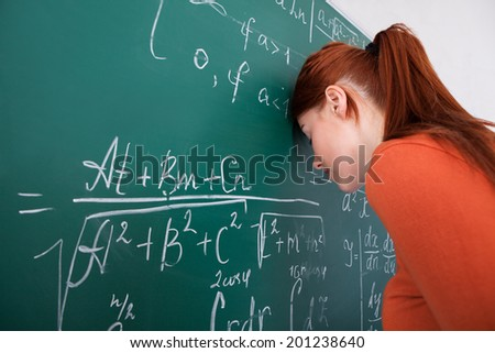 Side view of sad young female student leaning head on blackboard in classroom - stock photo