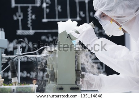 side-view of scientist in a chemistry lab analyzing under microscope around sprouted green plants and gas - stock photo