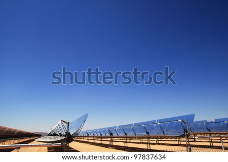 side view of SEGS solar thermal energy desert electricity plant with parabolic mirrors concentrating the sunlight with blue sky copy space - stock photo