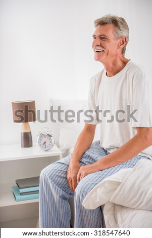 Side view of senior man is sitting on bed and smiling. - stock photo