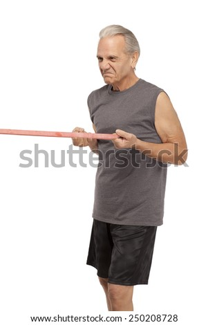 Side view of senior man pulling exercise rubber band system against white background - stock photo