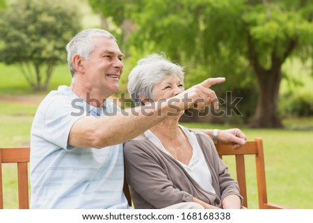 Side view of senior woman and man sitting on bench at the park - stock photo