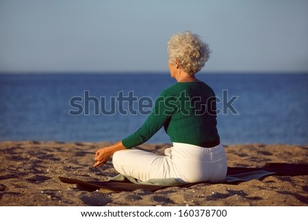 Side view of senior woman in meditation on the beach. Elderly woman sitting on the beach in lotus pose doing relaxation exercise . Mature woman doing yoga - stock photo