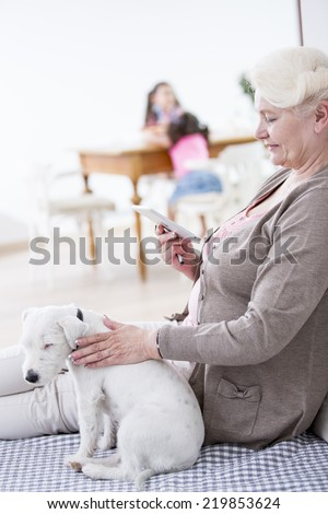 Side view of senior woman using digital tablet by dog at home - stock photo