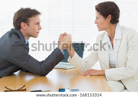 Side view of serious young business couple arm wrestling at office desk