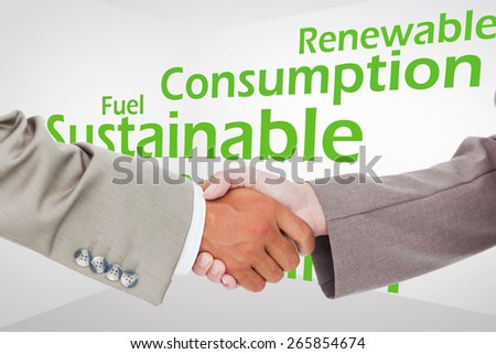 Side view of shaking hands against creative image of green economy concept - stock photo