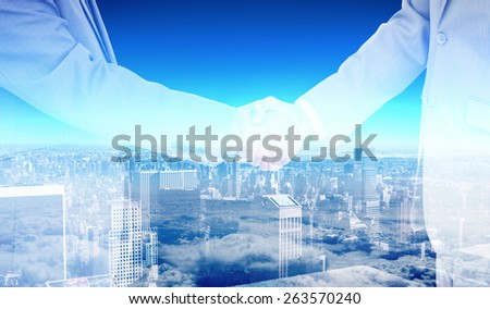 Side view of shaking hands against high angle view of city skyline - stock photo