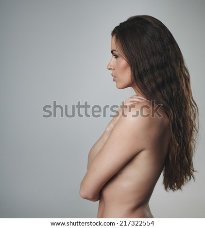 Side view of shirtless woman with beautiful curly long hair. Sexy female model on grey background - stock photo