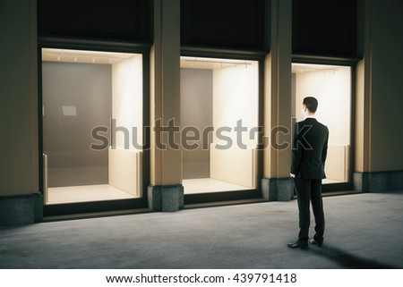 Side view of shop exterior design with glass showcase and looking businessman at night. Mock up, 3D Rendering