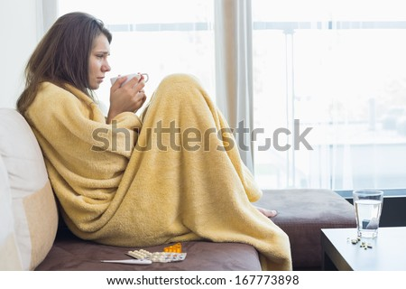 Side view of sick woman having coffee on sofa in living room - stock photo