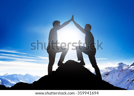 Side view of silhouette male friends giving high five on mountain peak - stock photo