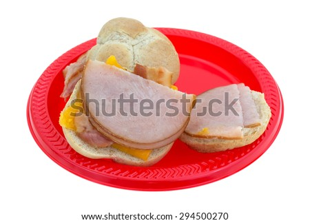Side view of small turkey sandwiches with bacon and cheddar cheese open on a red picnic plate. - stock photo