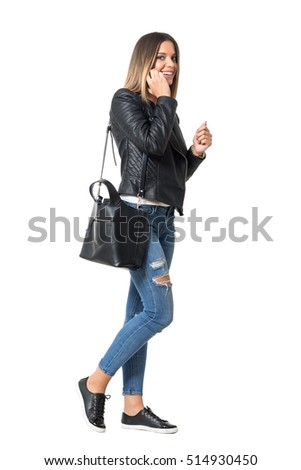 Side view of smiling beauty in casual street style clothes talking on the phone and looking at camera. Full body length portrait isolated over white background