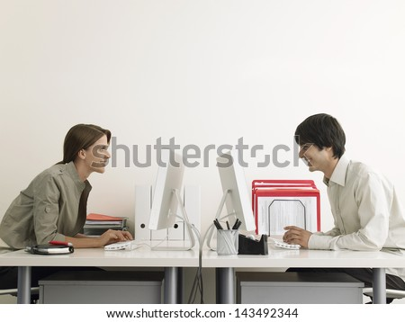 Side view of smiling business people using computers at office desks - stock photo