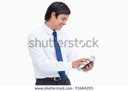 Side view of smiling tradesman using his tablet computer against a white background - stock photo