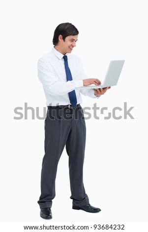 Side view of smiling tradesman working on his laptop against a white background - stock photo