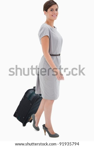 Side view of smiling woman with wheely bag against a white background - stock photo