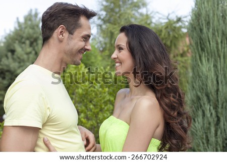 Side view of smiling young couple looking at each other in park - stock photo