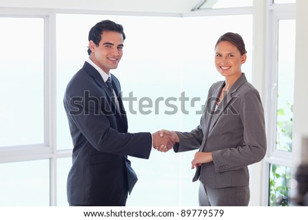 Side view of smiling young trade partner shaking hands