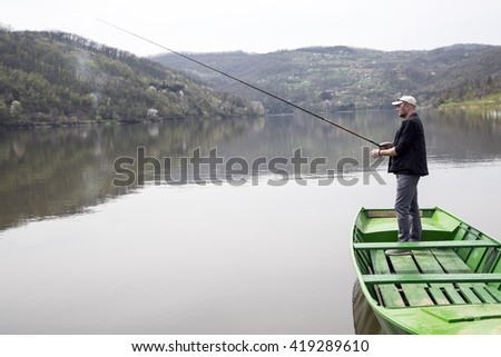 Side View Of Sport Fisher With Cap And Vest Fishing From  Green Canoe And Enjoying His Vacation On Beautiful Lake  - stock photo