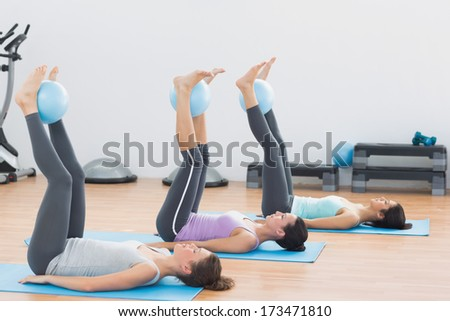 Side view of sporty young women holding balls between ankles in fitness studio