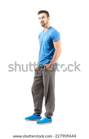 Side view of standing male in sportswear with hands in pocket. Full body length portrait isolated over white background. - stock photo