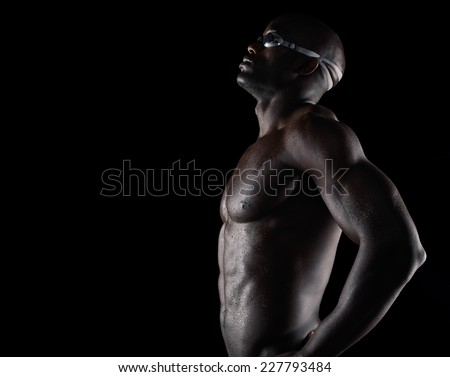 Side view of strong and muscular male athlete wearing swimming glasses standing with his hands on hips against black background with copy space. Fit african swimmer training for competition.