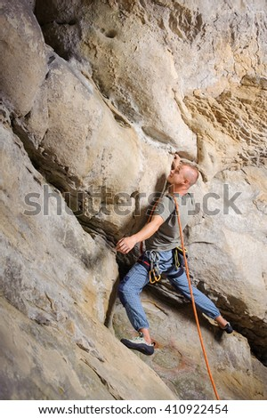 Side view of strong male lead climber climbing on big rock in the mountains. Man is searching for the next grip. Summer time. Climbing equipment - stock photo