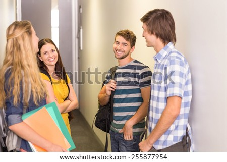 Side view of students with files standing at college corridor - stock photo