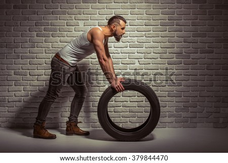 Side view of stylish man with beard leaning on a tire, standing against brick wall - stock photo