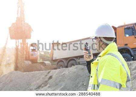 Side view of supervisor using walkie-talkie at construction site against clear sky - stock photo