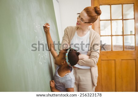 Side view of teacher looking at little girl write on blackboard in the classroom - stock photo