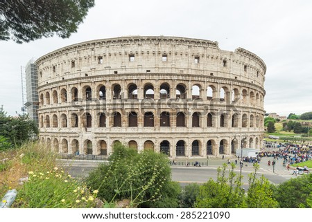 Side view of The Colosseum or Coliseum, also known as the Flavian Amphitheatre, in Rome city centre, Italy. Ruins of Roman Forum in the background. Cloudy sky, dramatic setting. - stock photo