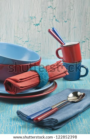 Side view of the kitchen utensils: red and blue plates, cups, spoons and napkins on a blue cracked background - stock photo