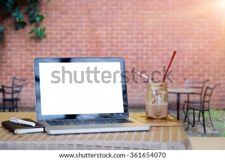side view of the laptop is on the work table in a conner outdoor with morning ligh. - stock photo