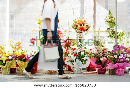 Side view of the lower body section of a young woman walking passed a fresh flowers market stall carrying a paper shopping bag during a sunny day outdoors. Faceless figure. - stock photo
