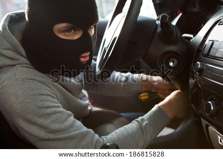 Side view of thief using screwdriver in car - stock photo