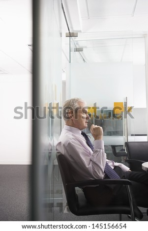 Side view of thoughtful middle aged businessman sitting on office chair - stock photo