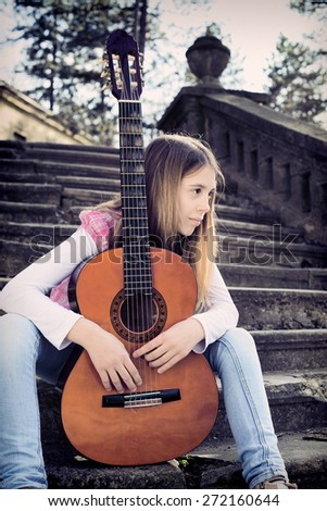 Side View of Thoughtful Young Girl With Guitar in Front of Her Sitting on the Foot of the Stairs and Looking into the Distance  - stock photo