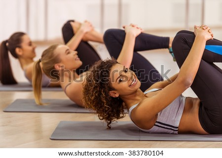 Side view of three attractive sport girls smiling while working out lying on yoga mat in fitness class. Beautiful Afro-American girl looking at camera - stock photo