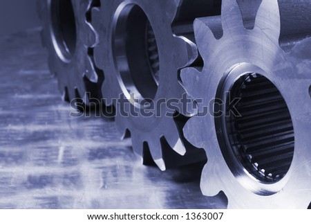 side view of three cogs in bluish against stainless-steel